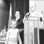 Tėvų komiteto pirmininkas Vytas Mačiulis su dukra Olivija ir komiteto narė Aušra Baron įteikia prizus loterijos laimėtojams.