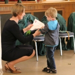 Young student Jokubas receives his certificate for stepping into the world of Lithuanian Language