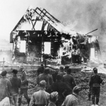 German soldiers and locals watch a Lithuanian synagogue burn on July 9, 1941. (German Federal Archive)